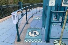 Abstandsmarkierungen auf dem Boden und Spender mit Handdesinfektionsmittel