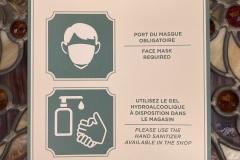 Hinweisschild mit Aufforderungen zum Tragen von Gesichtsmasken und Desinfizieren der Hände