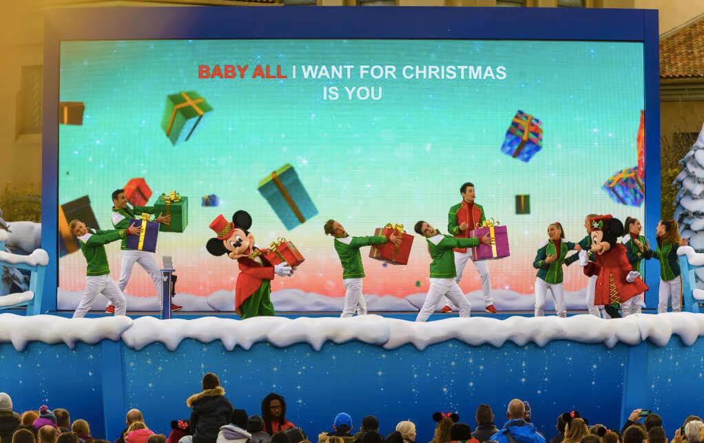 Mickey und Sänger auf einer Bühne mit Geschenken