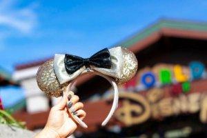 eine Hand hält die goldglitzernden Mickeyohren in die Luft