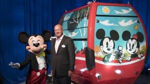 Mickey Mouse steht vor einer Gondel des Disney Skyliners