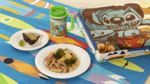 zwei Teller mit Essen und ein Trinkbecher liegen auf einem Handtuch