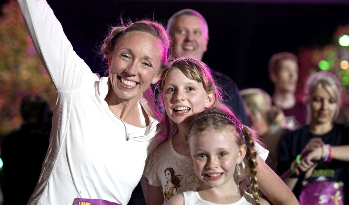 eine Frau mit zwei Mädchen strahlt fröhlich in Richtung der Kamera