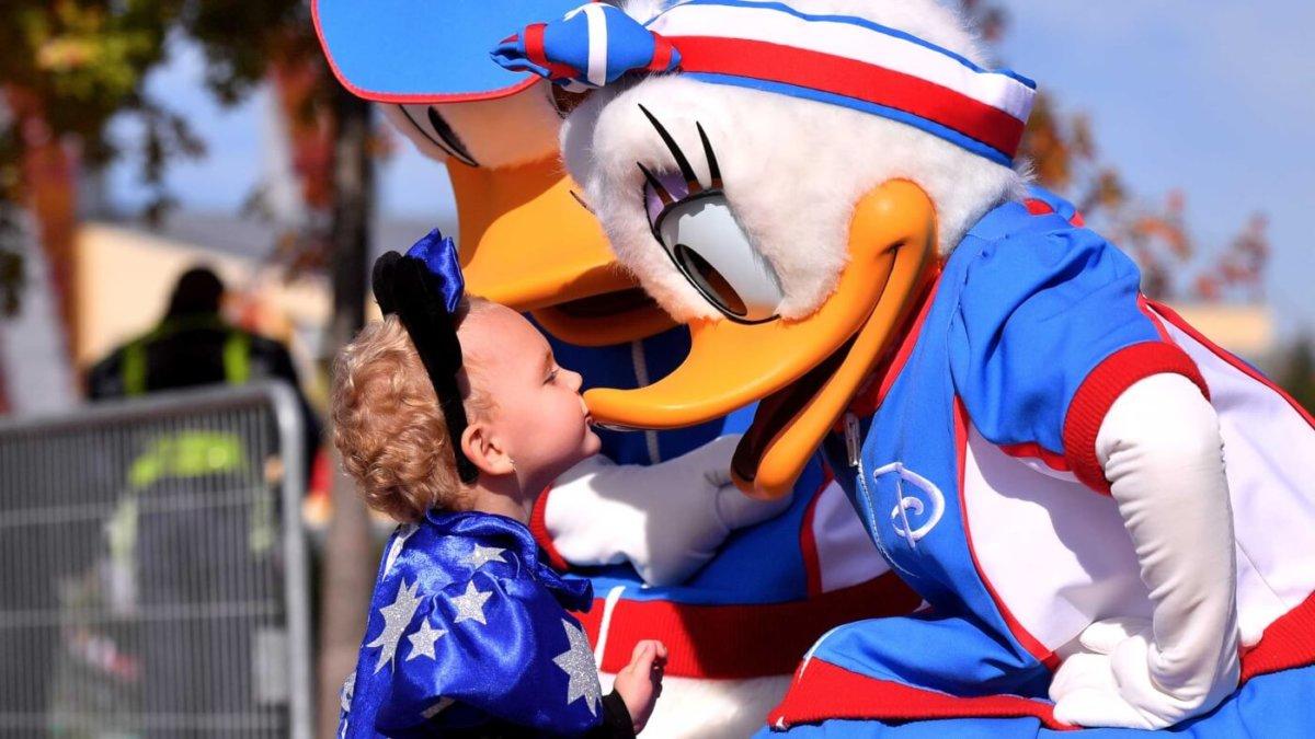 ein kleines Kind gibt Daisy Duck einen Kuss auf den Schnabel