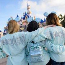Drei junge Damen präsentieren Spirit Jersey, Rucksack und Mickey Ohren im neuen Farbton Arendelle Aqua
