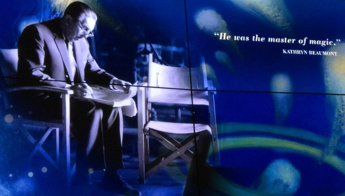 Walt Disney sitzt auf einem Stuhl und zeichnet