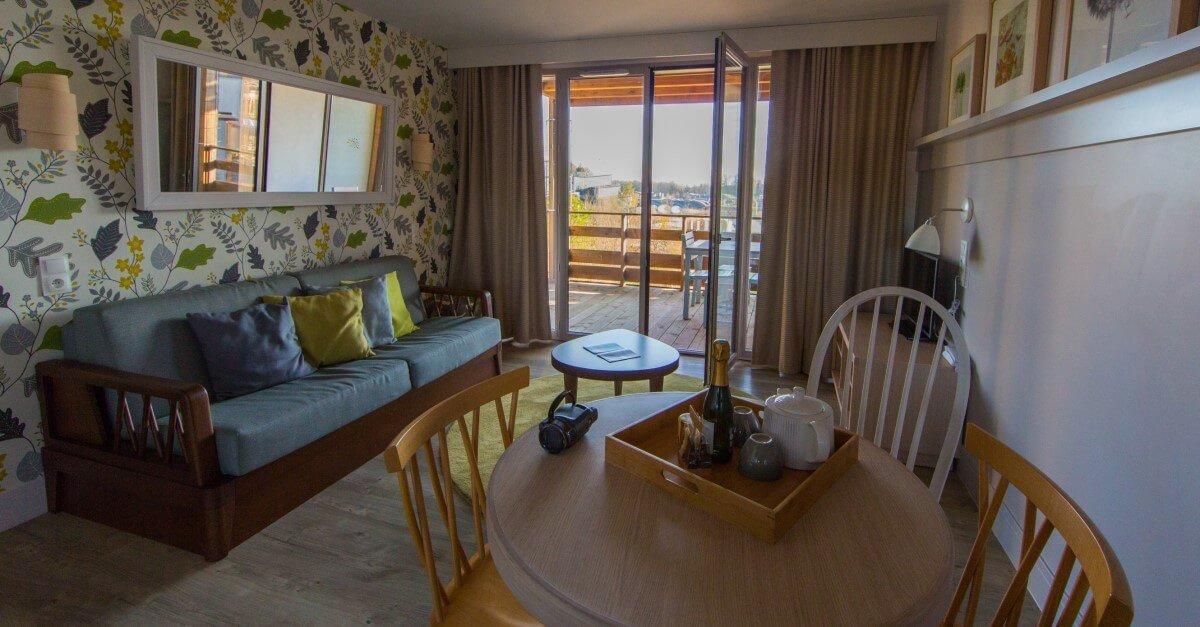Ferienwohnung Wohnzimmer mit Sofa, Esstisch und Balkon