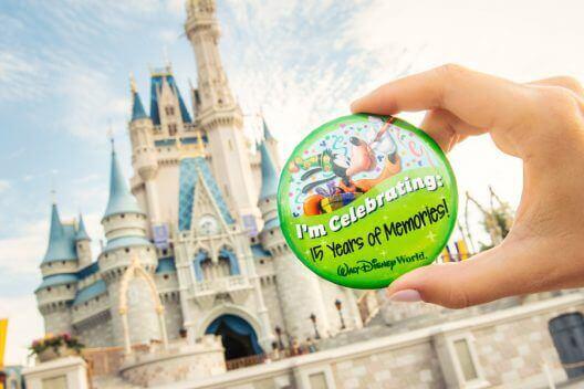 """Eine Hand hält einen Button mit der Aufschrift """"I'm Celebrating 15 Years of Memories"""" vor dem Cinderella Castle in die Höhe"""