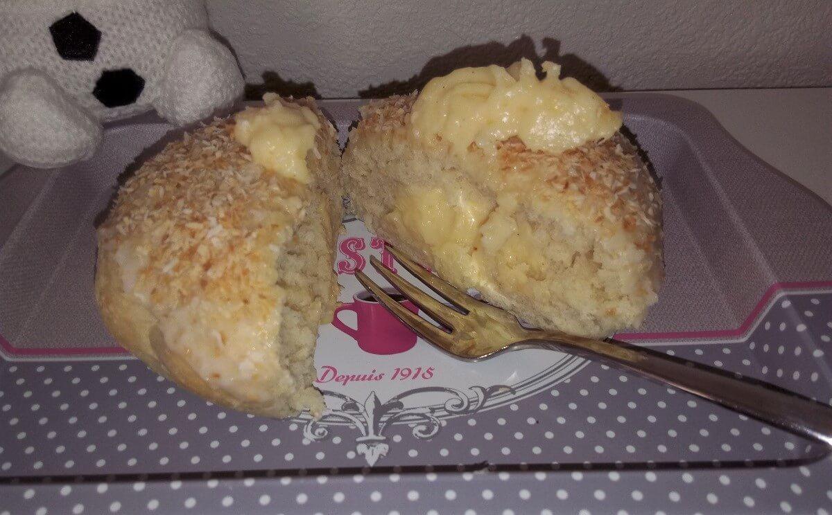 auf einem kleinen Tablett liegt ein in der Mitte aufgeschnittenes School Bread mit einer Kuchengabel