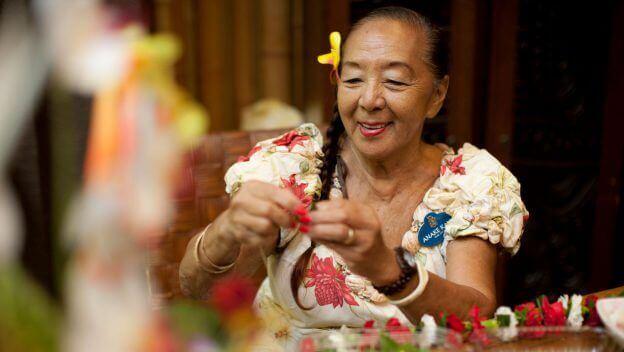 Aunty Kau'i aus dem Polynesian Village Resort beim Erstellen einer Lanai-Blumenkette