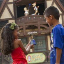 Zwei Kinder stehen mit Mobiltelefon vor einem Pavillion