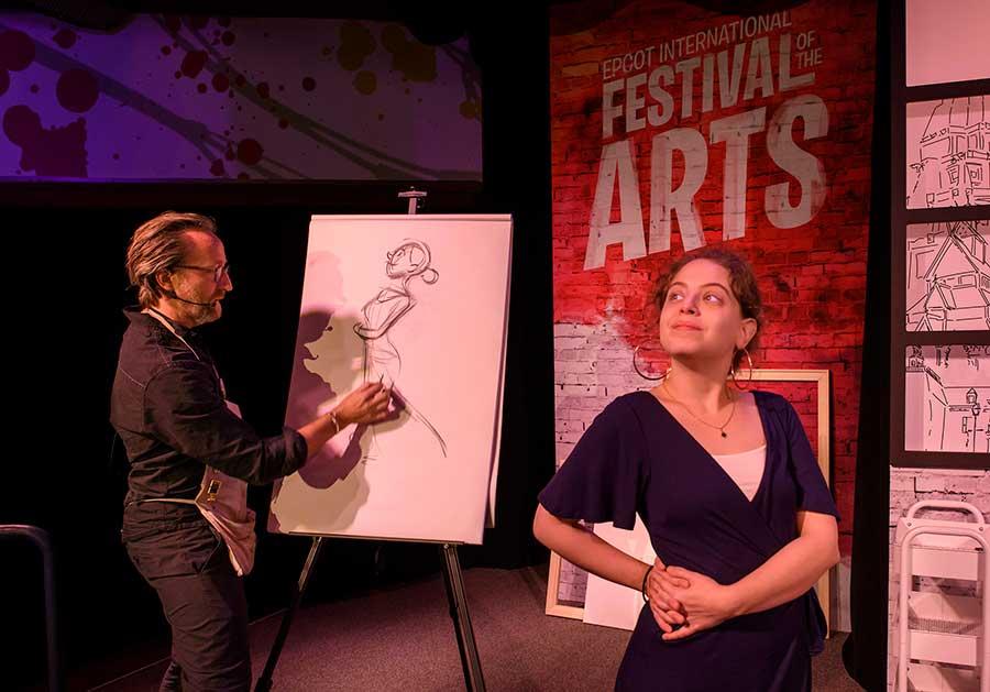 Ein Künstler zeichnet beim Festival of the Arts eine junge Frau, die für ihn posiert