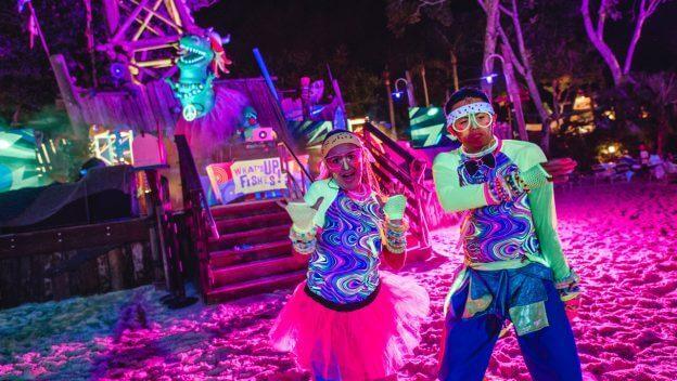 zwei bunt gekleidete Personen tanzen bei der H2O Glow Night im Typhoon Lagoon Wasserpark