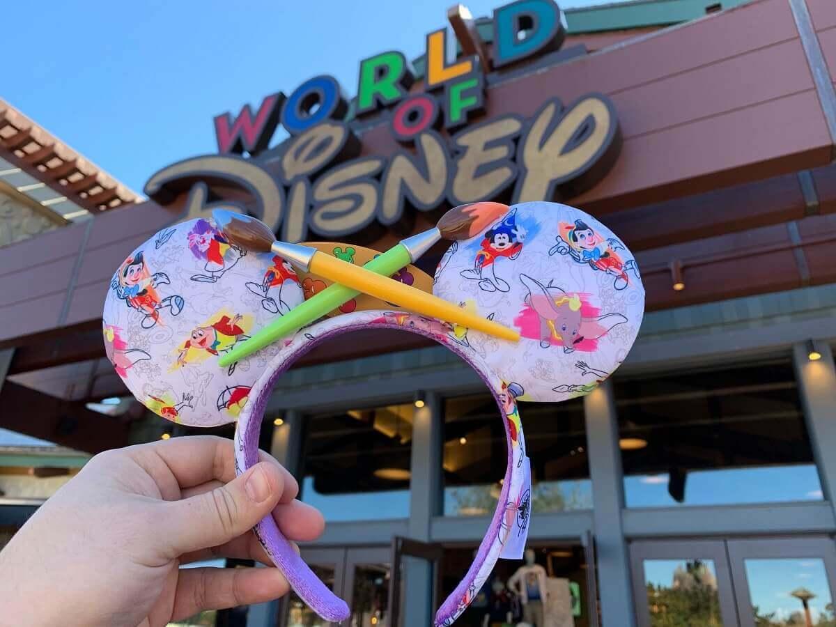 """Eine Hand hält ein Paar farbenfrohe Mickeyohren im """"Ink & Paint""""-Design vor dem World of Disney Store in Disney Springs in die Höhe"""