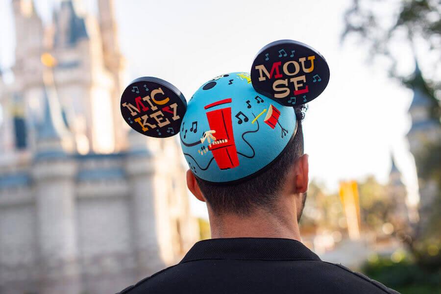 Ein Mann, der von hinten zu sehen ist, trägt einen Mickey Ear Hat-Hut vor dem Cinderella Castle
