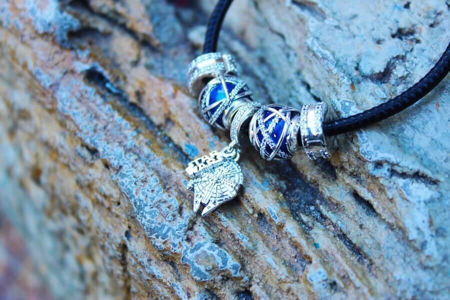 ein Pandora-Armband mit verschiedenen Anhängern ist vor einem Baumstamm zu sehen