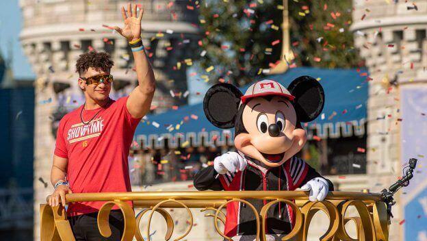 Patrick Maholmes und Mickey Maus winken von einem Wagen bei der Parade im Magic Kingdom