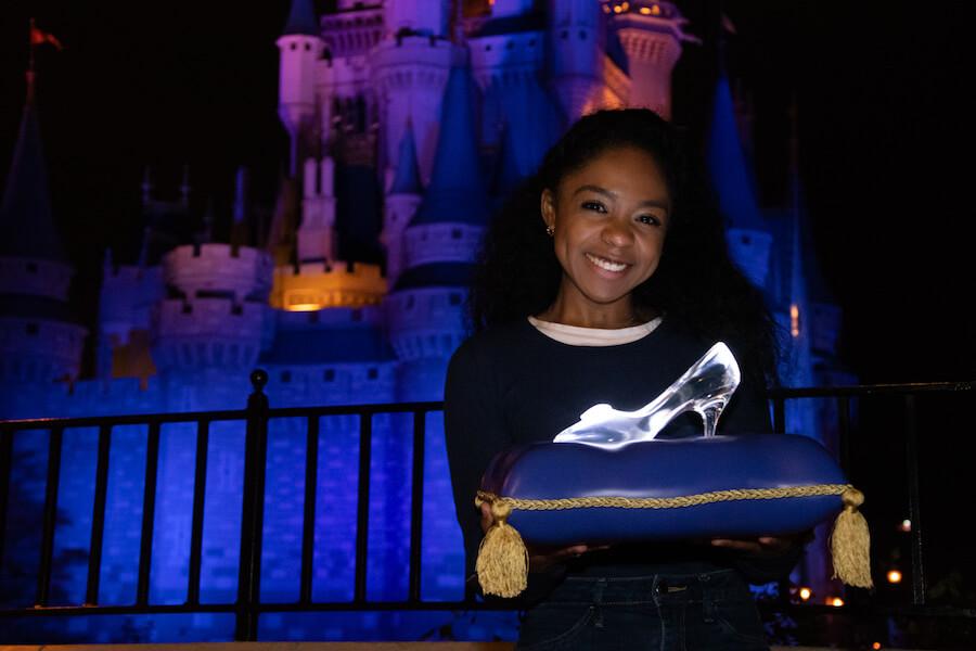 eine junge dunkelhäutige Frau hält ein Kissen mit Cinderellas Glasschuh vor dem Cinderell Castle in den Händen und lächelt in die Kamera