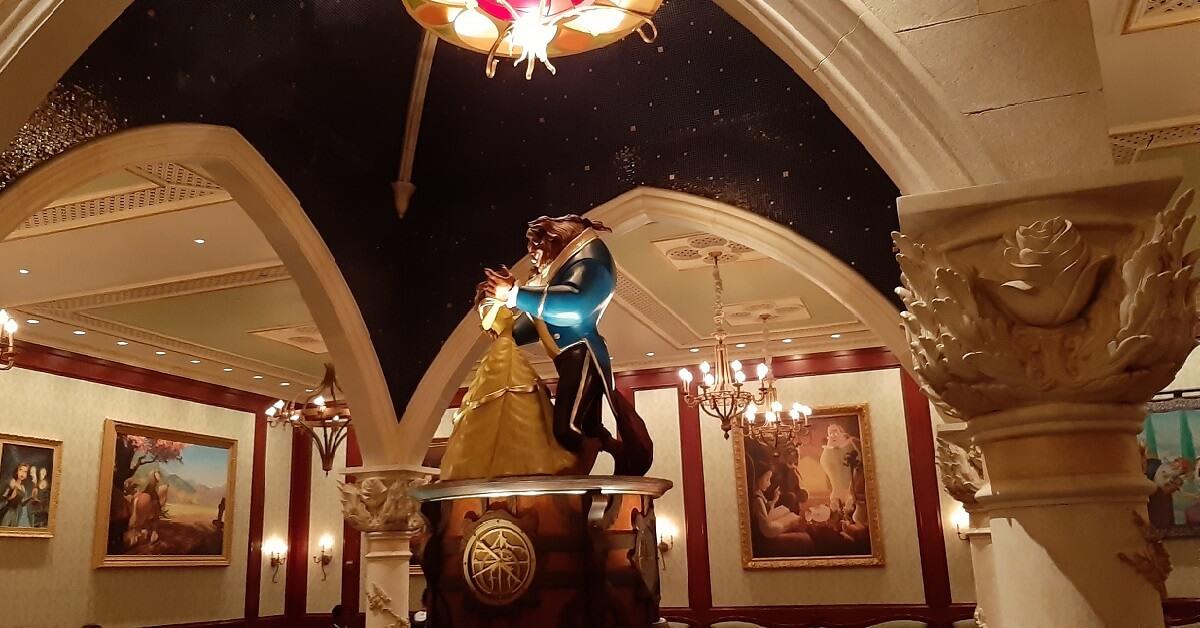 Blick in die Bildergalerie im Be Our Guest Restaurant und auf die in der Mitte des Raums stehende große Spieluhr