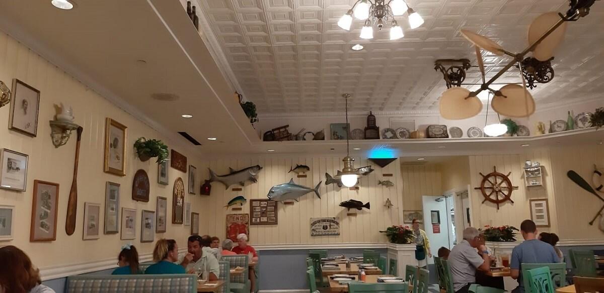 Blick in den Gastraum von Olivias Cafe im Old Key West Resort mit verschiedenen Sitzbereichen und Dekorationen an den Wänden