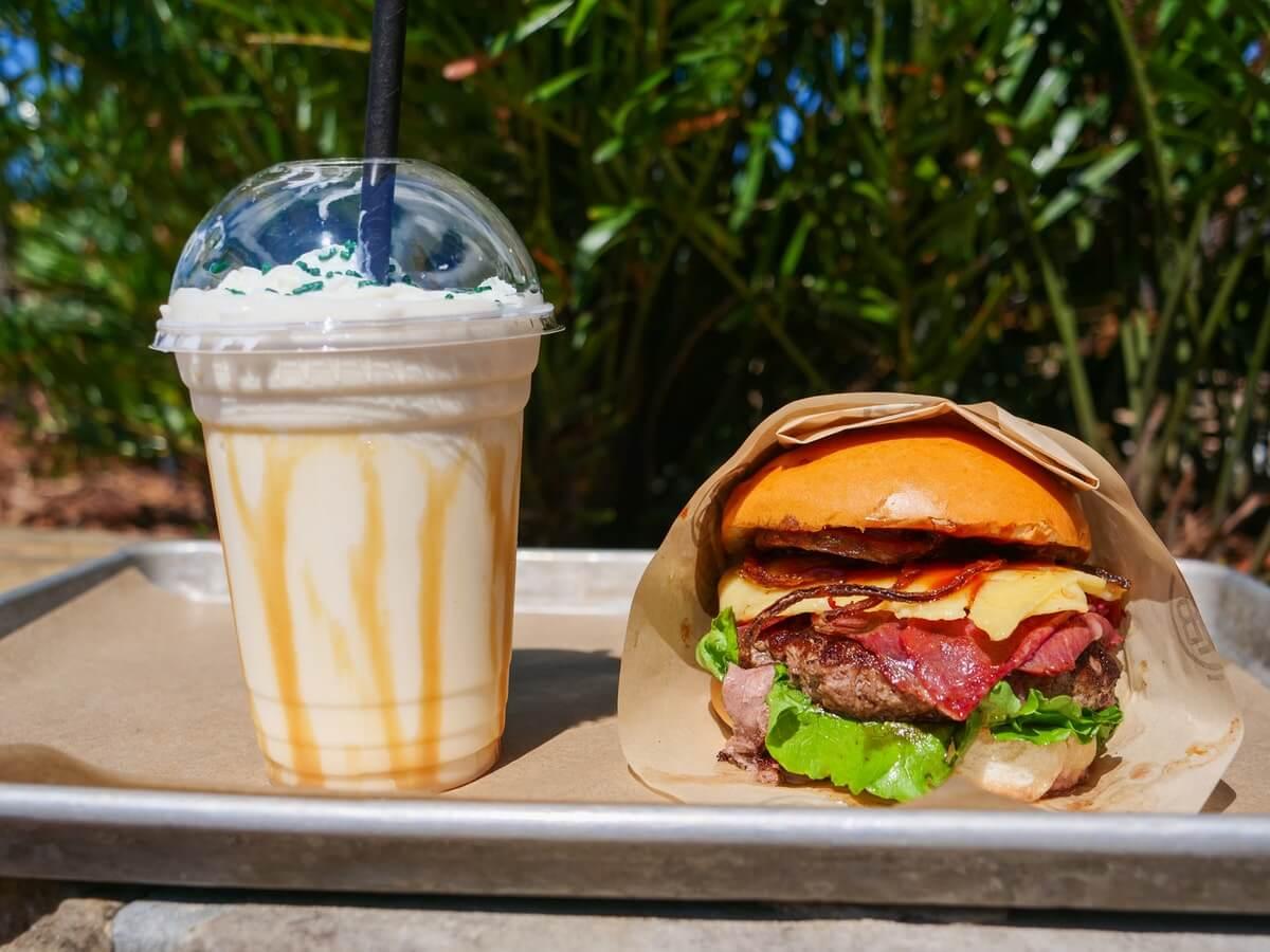 auf einem Tablett steht ein Shake in einem Plastikbecher neben einem Burger