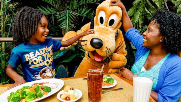 Pluto besucht eine Mutter und ihren Sohn an einem Tisch im Restaurant Garden Grill in Epcot