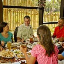 Mehrere Besucher essen gemeinsam mit einem Tierspezialisten im Sanaa in der Animal Kingdom Lodge
