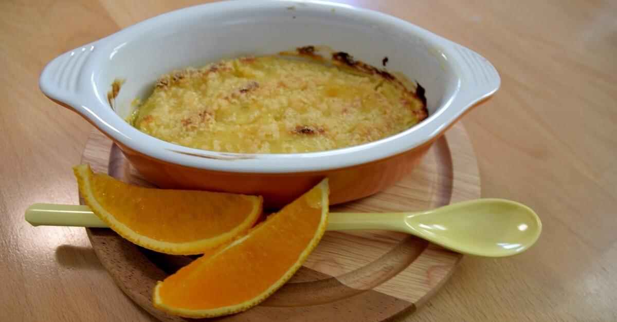 Auf einem kleinen runden Holztablett liegen eine kleine Schale mit Crema Catalana, ein langer Dessertlöffel und Orangenspalten
