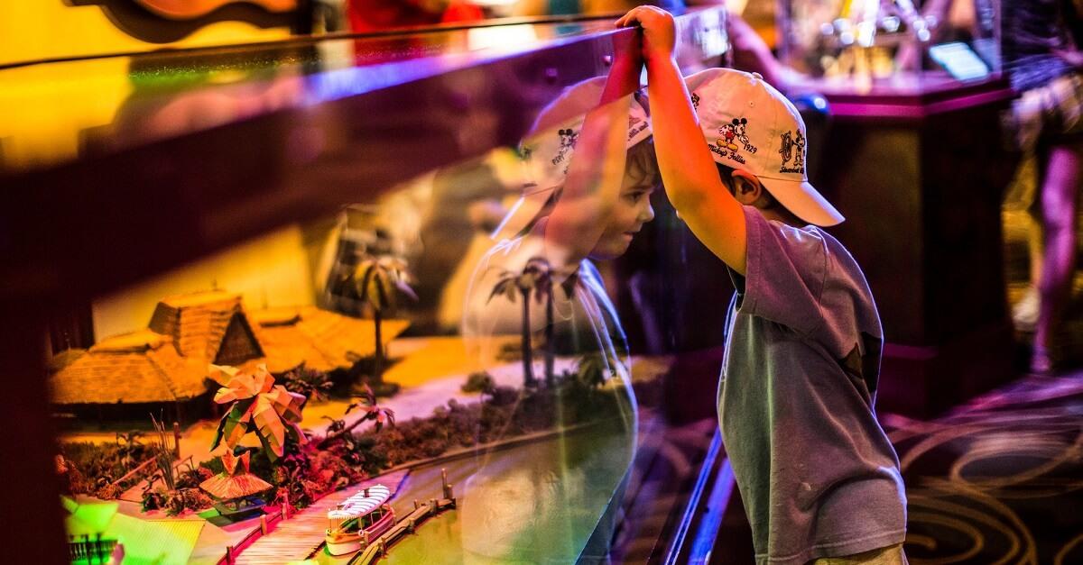 Ein kleiner Junge sieht sich fasziniert ein Modell in der Ausstellung Walt Disney Presents in den Hollywood Studios an