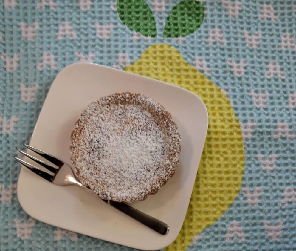 Eine kleine Zitronentarte auf einem Tellerchen mit einer Kuchengabel