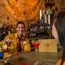 Eine Barkeeperin bereitet in Jock Lindsey's Hangar Bar einen Cocktail vor den Augen einer Besucherin zu