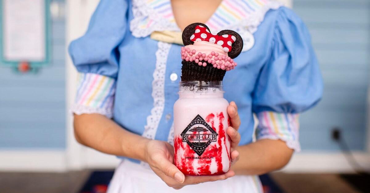 Eine Mitarbeiterin aus dem Beaches & Cream Soda Shop hält einen Minnie Milchshake in ihren Händen