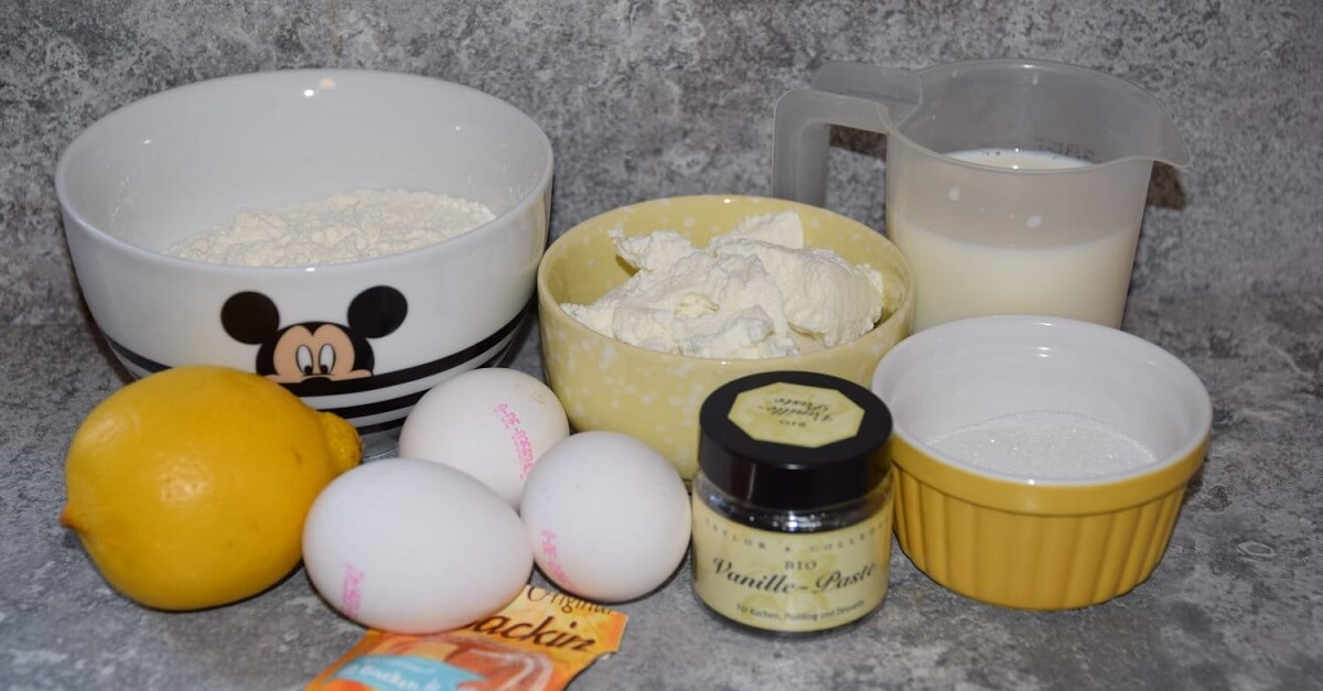 Auf einer Küchenarbeitsfläche stehen verschiedene Zutaten für die Zubereitung von Zitronen Ricotta Pancakes