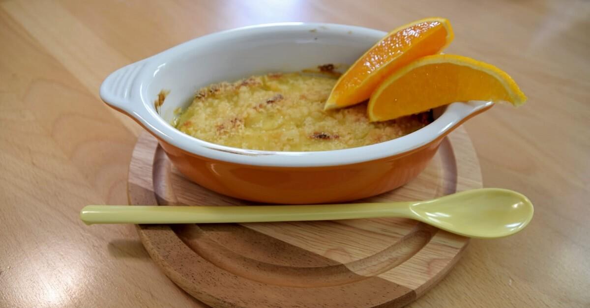 In einem feuerfesten Schälchen sind eine Portion Crema Catalana und zwei Orangenspalten zu sehen