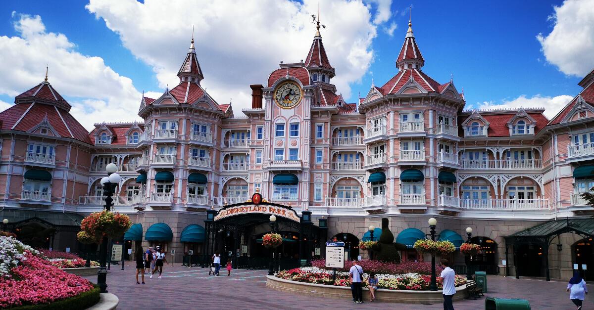 Die Eingangsfassade imponiert und ist teil des Disneylandhotels, umgeben von unzähligen Blumen.