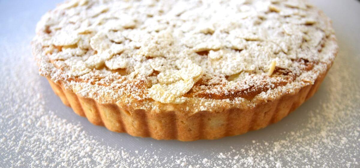 Auf einem Schneidebrett liegt der fertige und mit Puderzucker bestäubte Apple Pie