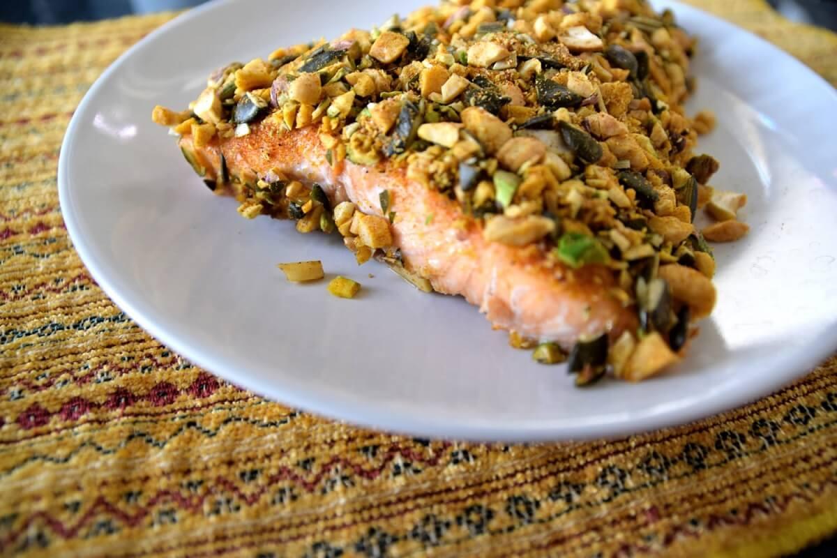 Auf einem weißen Teller liegt das fertig gebackene Lachsfilet mit Nusskruste