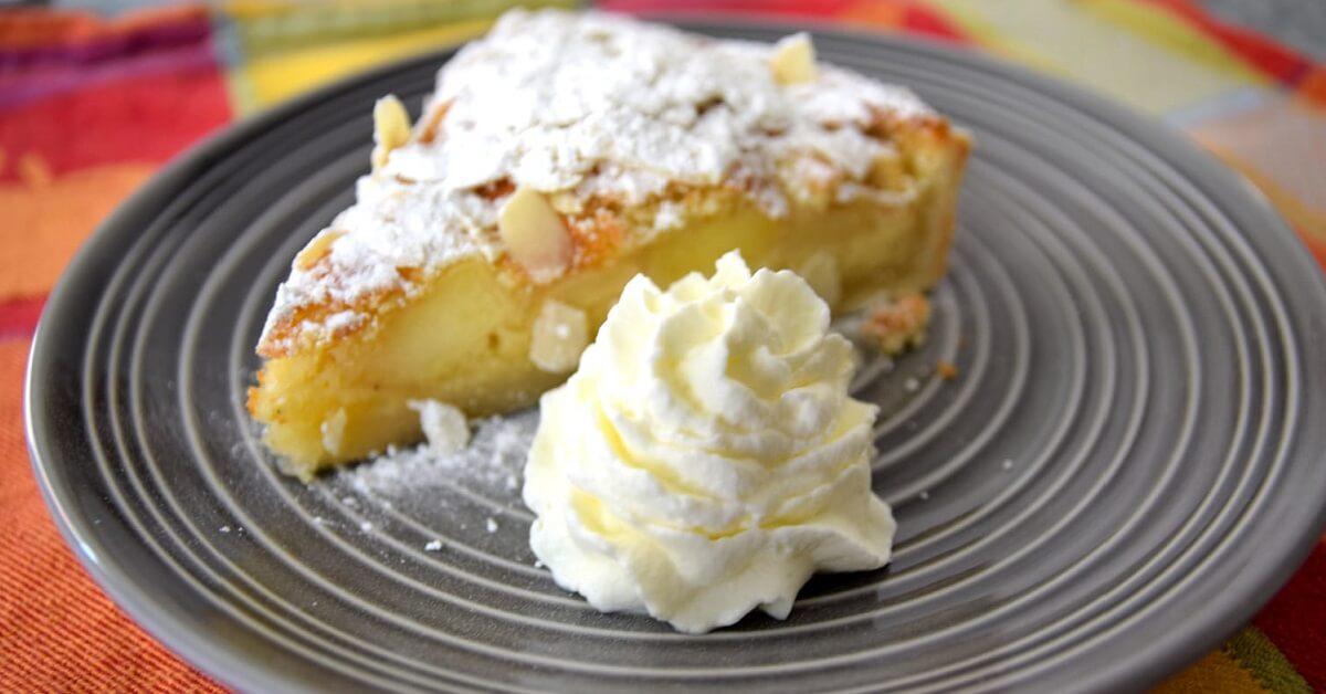 Auf einem grauen Teller ist ein Stück mit Puderzucker bestäubter Apfelkuchen mit Sahne zu sehen