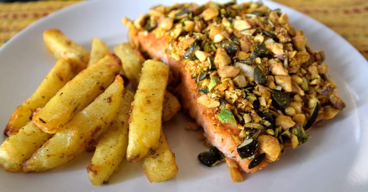 Auf einem Teller liegen ein Stück Lachs mit Nusskruste und daneben mediterrane Pommes