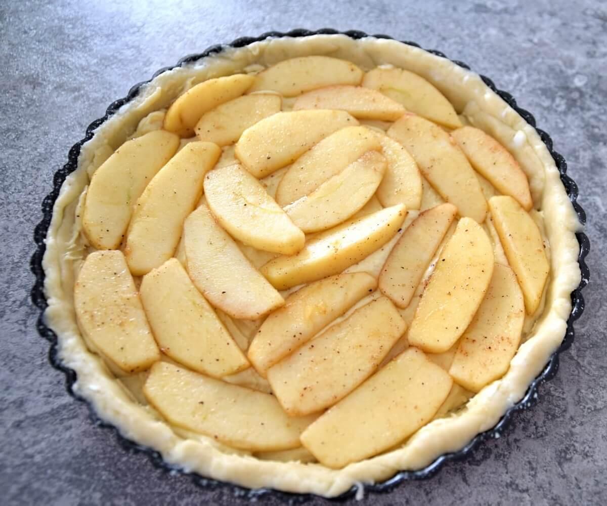 In einer Tarteform befinden sich der Teig und die gedämpften Apfelscheiben für den Apfelkuchen
