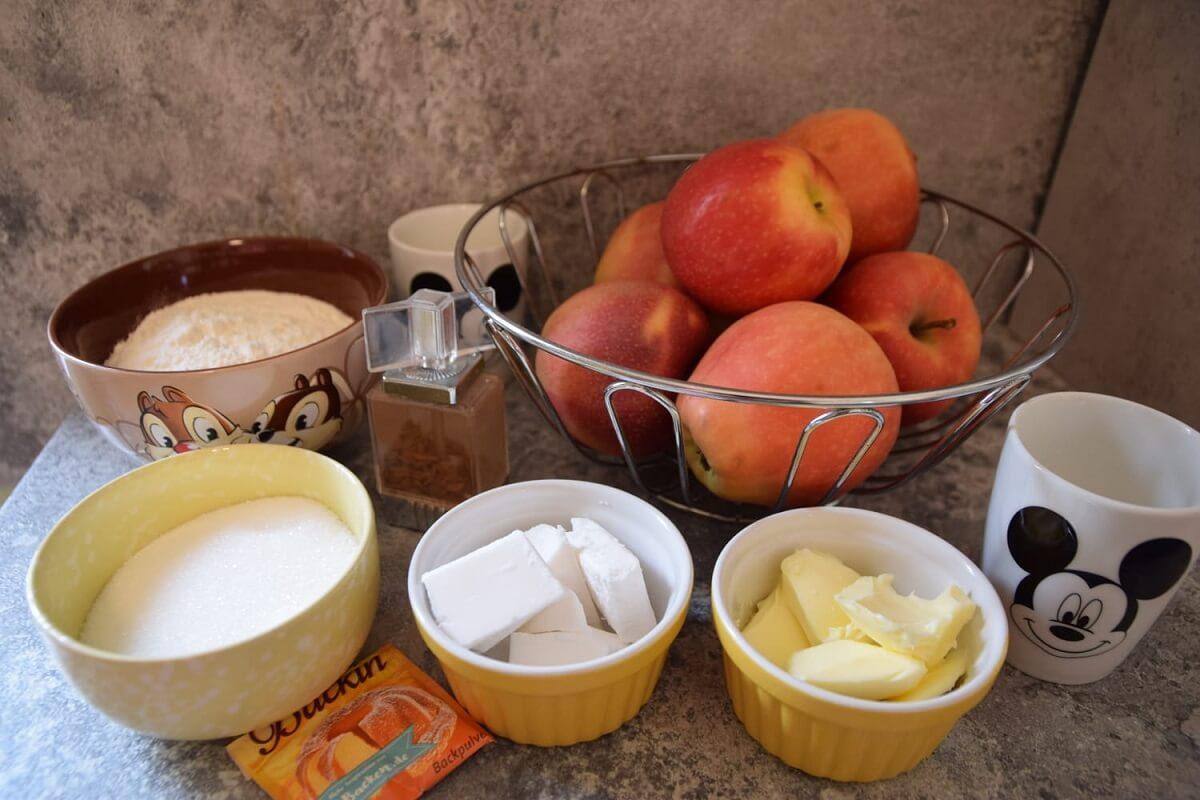 Auf einer Küchenarbeitsfläche sind mehrere Zutaten für den Apple Pie zu sehen