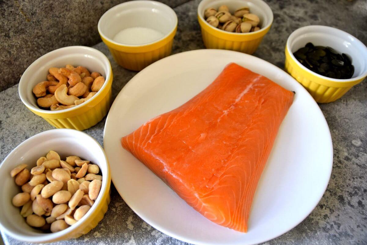 Auf einem Teller liegt ein Stück Lachsfilet, darum herum stehen mehrere Schälchen mit verschiedenen Nüssen und etwas Zucker