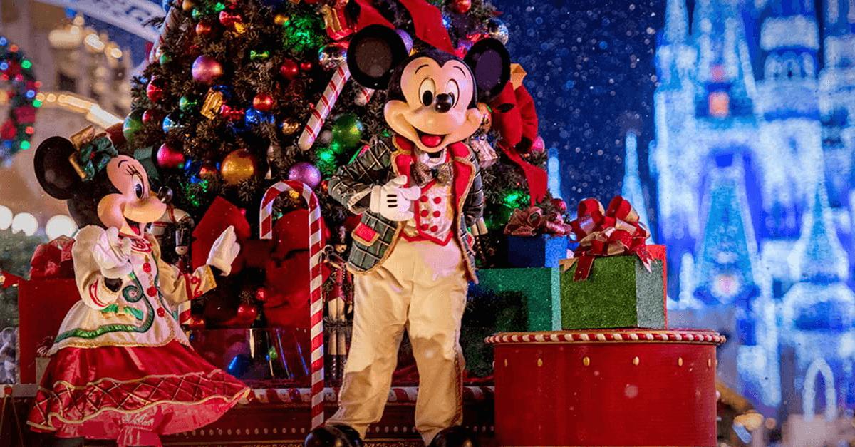 Mickey und Minnie Mouse in festlicher Kleidung auf einem Paradewagen auf der Main Street U.S.A. vor dem Cinderella Schloss bei festlicher Beleuchtung