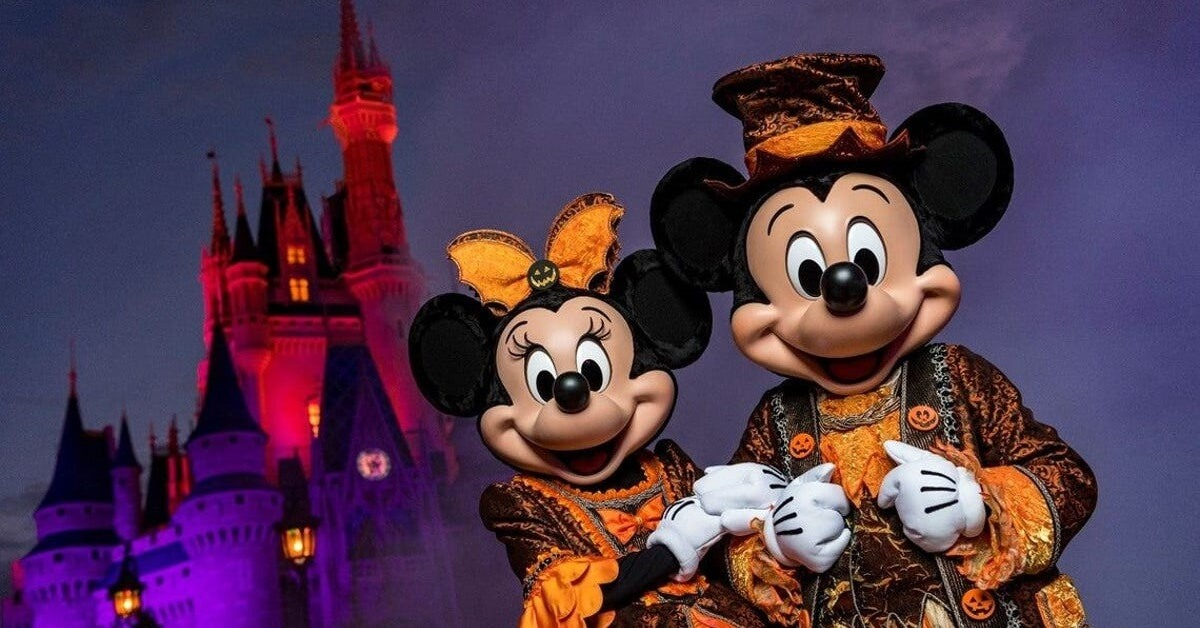 Mickey und Minnie stehen in orange-schwarzen Halloweenkostümen vor dem Cinderella Castle im Magic Kingdom