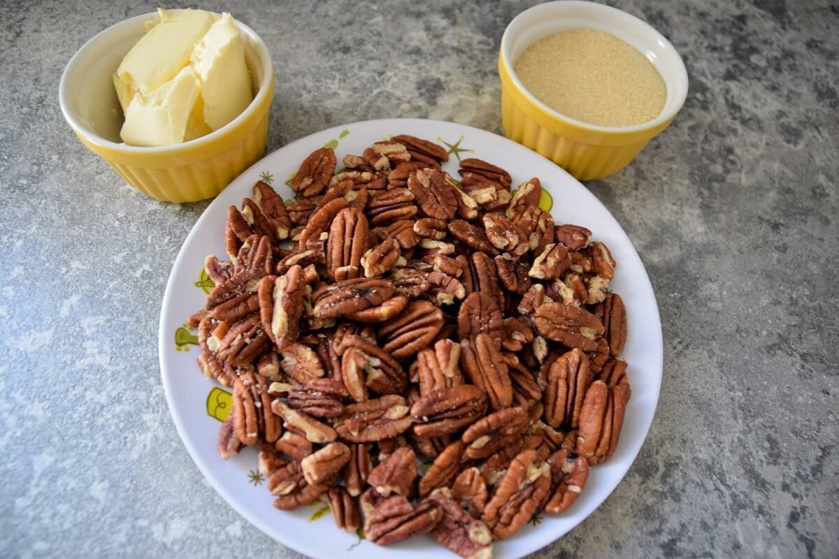Ein Teller mit Pekannüssen und zwei Schälchen mit Butter und braunem Zucker sind in Form von Mickeys Kopf platziert