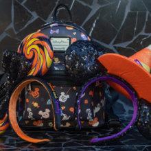 An einen Loungefly-Rucksack mit Halloween-Print sind zwei verschiedene Minnie-Haarreifen in Halloween-Designs gelehnt