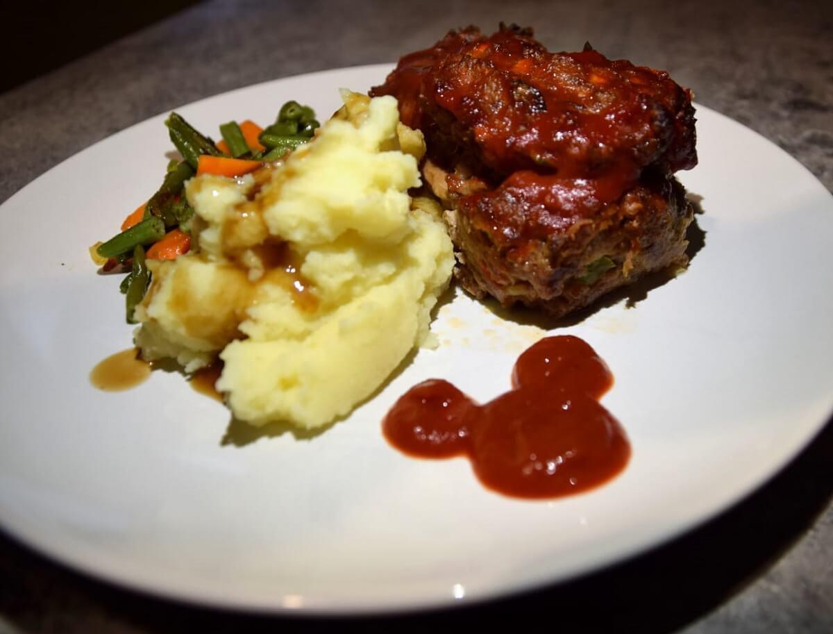 Auf einem großen weißen Teller ist ein kleiner Hackbraten mit Kartoffelpüree und Gemüsebeilage serviert