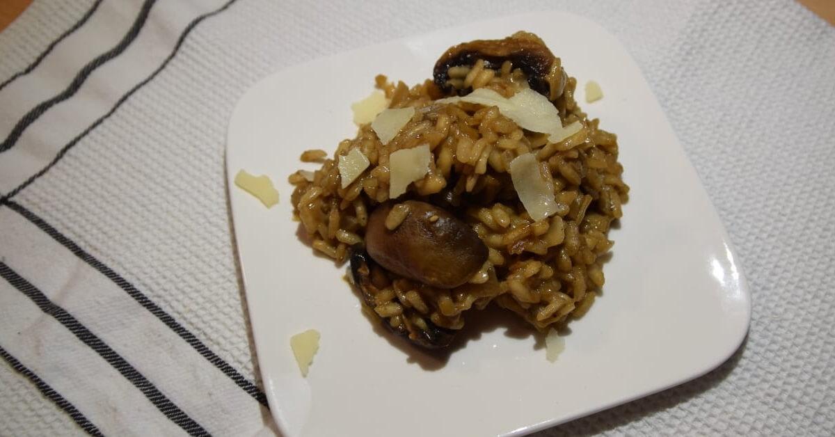 Auf einem kleinen quadratischen Teller ist eine Portion des Pilzrisottos angerichtet