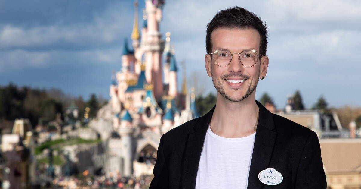 Der Cosmetology Designer Nicolas Cueff steht im Disneyland Park vor dem Dornröschenschloss im Hintergrund