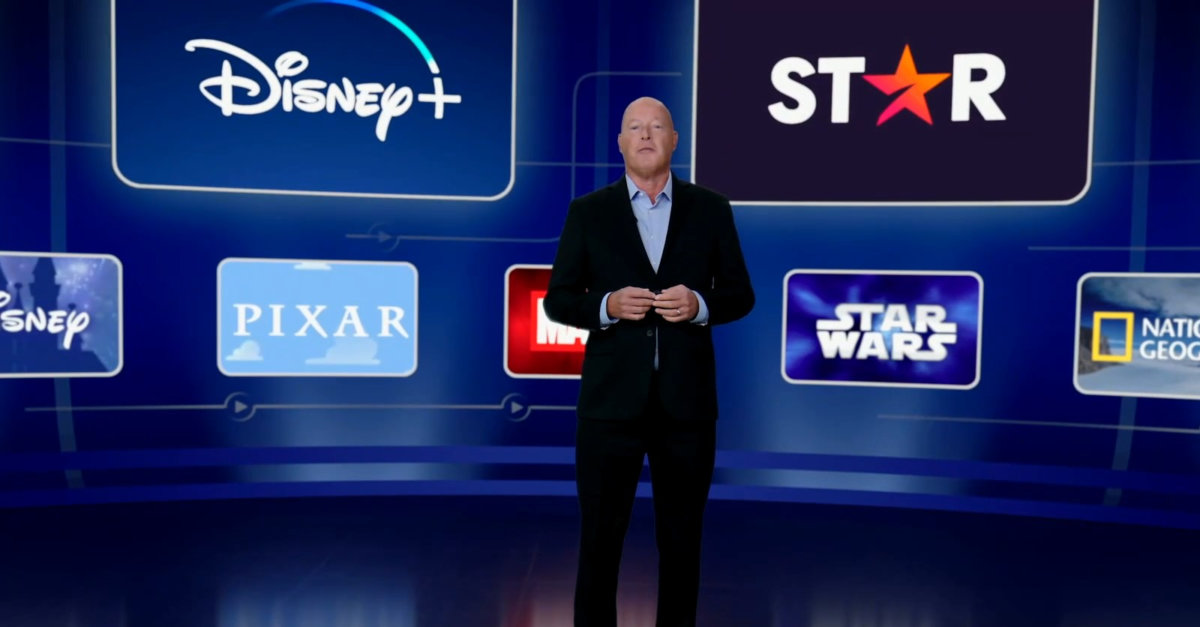 Bob Chapek präsentiert auf einer Bühne die aktuellen Zahlen des Unternehmens. Hinter ihm ist eine Videowand, welche die Logos der Unternehmensteile zeigt.